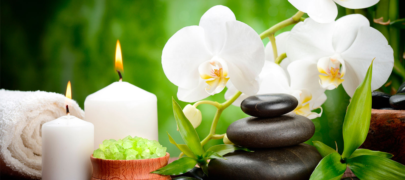Spa environment with candle, towel, stone & flowers with green leaves