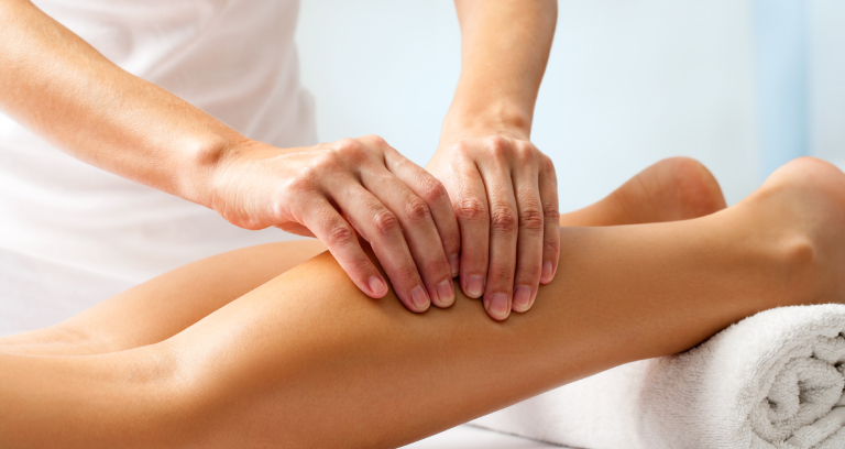 A Massage Therapist Doing Leg Massage For Her Patient.