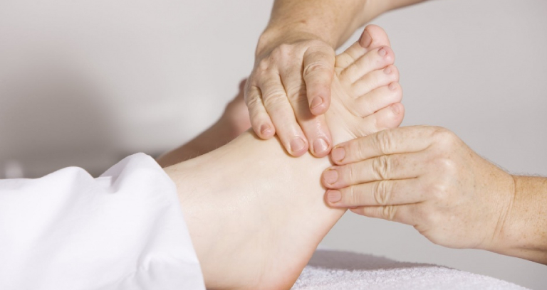 A Woman Experiencing Feet Massage Therapy.