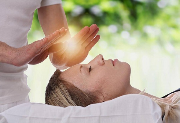 A Reiki Specialist Giving Healing Therapy To A Young Woman.