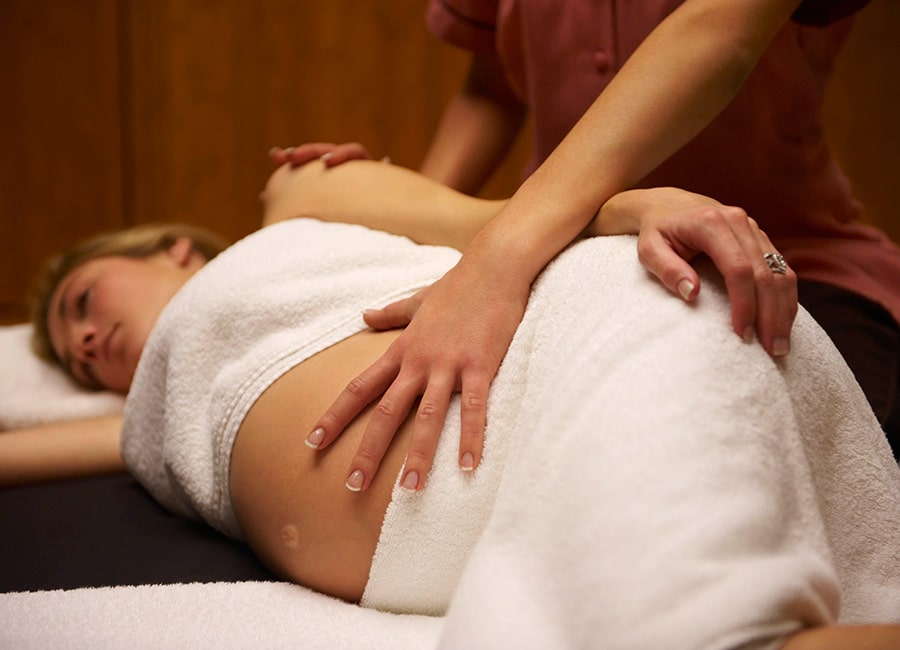 A Side View of Pregnancy Woman Getting Reiki Massage.