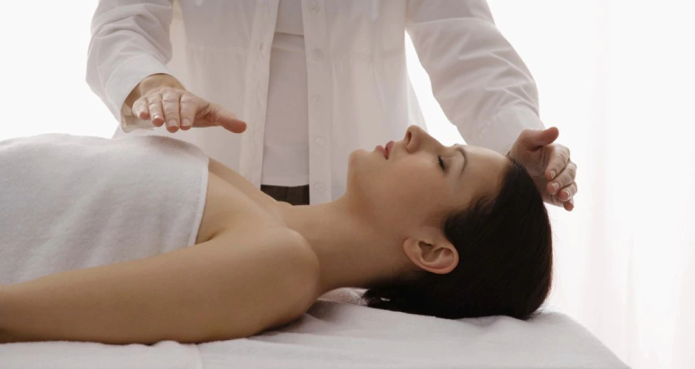 A Reiki Specialist Treating His Patient.