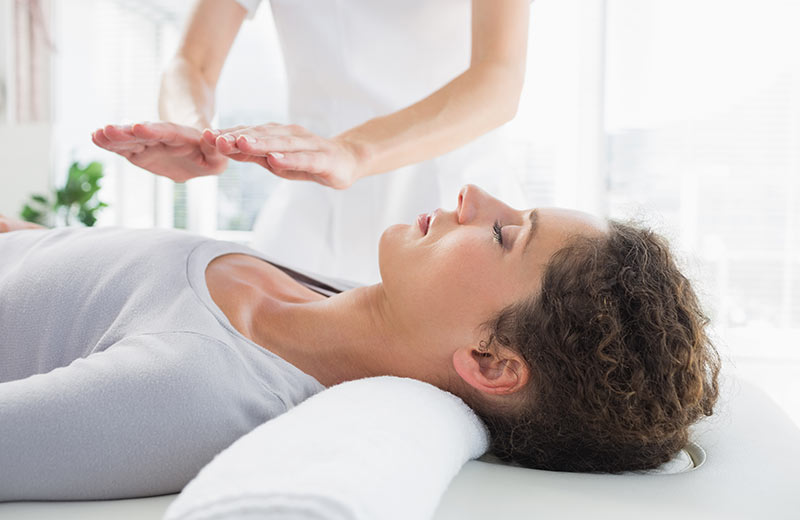 A Woman getting Relaxed During Her Reiki Session.