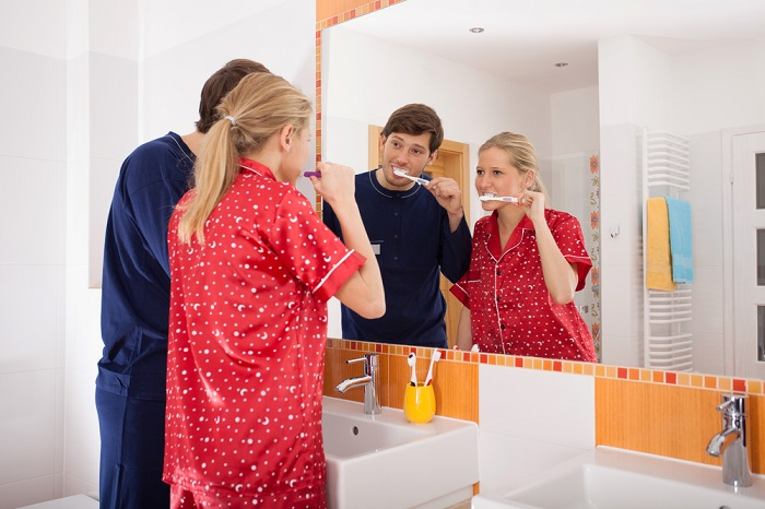 A couple brushing their teeth while looking at the mirror in the bathroom