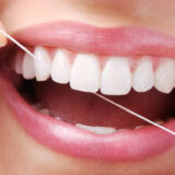 Image represents A smiling person cleaning her teeth and gums with dental floss